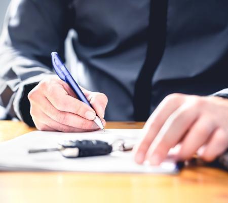 Osoba podpisuje dokument, naktórym leżą kluczyki samochodowe