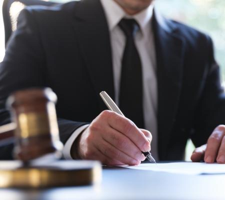 Osoba podpisuje dokument obok młotka sędziowskiego