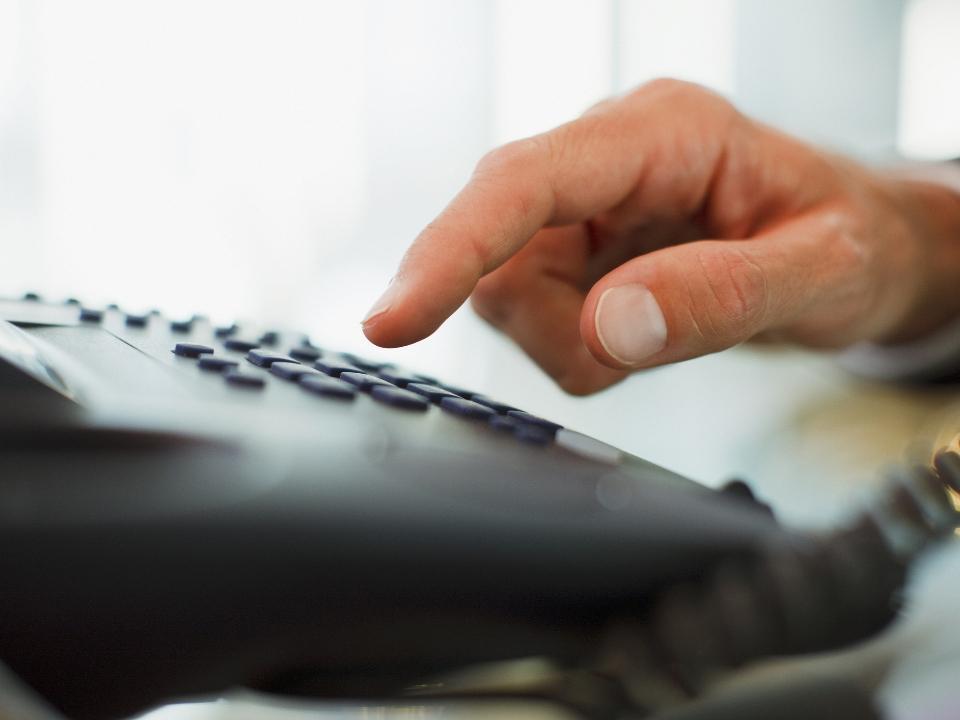 Osoba wybiera numer telefonu nastacjonarnym aparacie telefonicznym